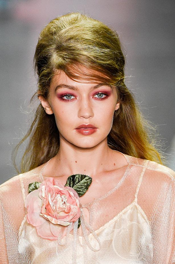 Gigi worked the pink eye trend, spider-lash mascara and nude gloss lips at the Anna Sui SS17 show, quickly making magenta the It girl shade for green eyed girls.