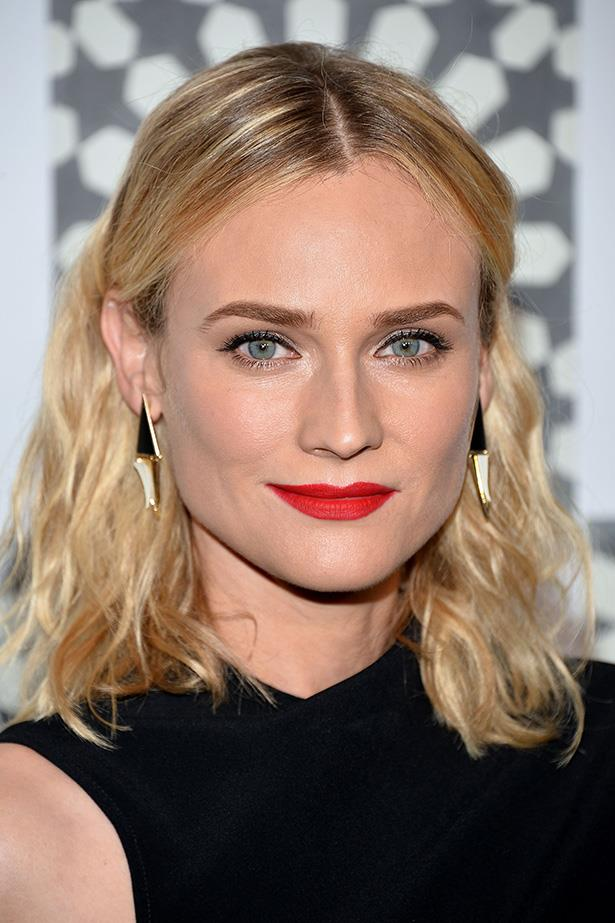 **Diane Kruger** <br> <br>  The slick middle part and waves, the earrings and that blue-toned red lip...This is the ultimate after-work combo.