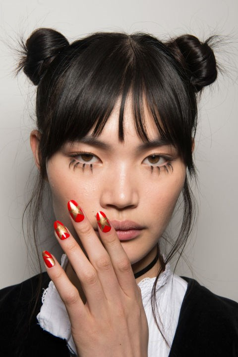 """<strong>Jeremy Scott</strong> <br><br> The look: Pro manicurist Miss Pop created a Hollywood Walk of Fame-inspired nail. """"I added graphic gold stars rising up the nails, boldly standing front and center, and co-starring in corners,"""" she explains. """"It's an element that takes that aspirational glamour of L.A. and makes it DIY."""" <br><br> The kit: A custom mix of CND Vinylux Weekly Polish in Banana Clips and Electric Orange, topped with a layer of Wildfire."""
