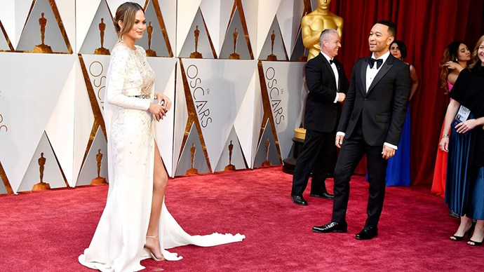 John Legend looks dotingly on Chrissy Teigen as she poses for the paparazzi.