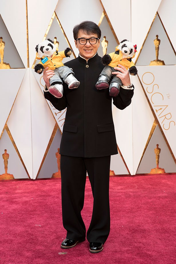Jackie Chan posed with a couple of panda plush toys.