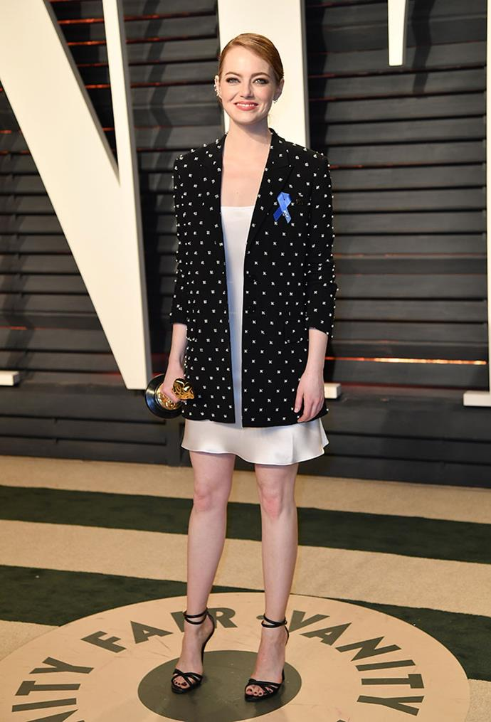 Emma Stone changed for the <em>Vanity Fair</em> Oscars party and swapped her Planned Parenthood pin for the blue ACLU ribbon. (Another new accessory: that Oscars statuette.)