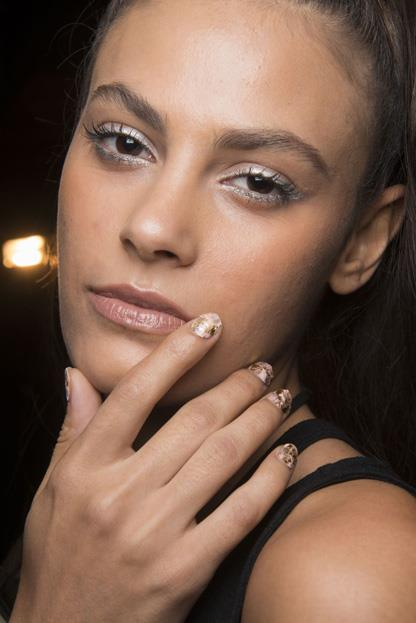 """<p><strong>Nicholas K </strong> <br><br> <p>Nail artist <a href=""""http://misspopnails.com/"""">Miss Pop</a> took inspiration from the Jordanian Desert for the look at Nicholas K. She started with a <a href=""""https://www.shopncla.com/collections/nail-wrap/products/that-warm-november-night"""">NCLA's Classics Nail Wraps in 'That Warm November Night' </a>and filed them down to shape. She added wavy bands in alternating shades of <a href=""""https://www.shopncla.com/collections/nudes"""">nude </a>polish, then applied gold foil from her collab <a href=""""http://misspopnails.com/miss-pop-x-tattify"""">Miss Pop x Tattify</a> in So Fancy. Once set she sealed the look with a clear topcoat."""