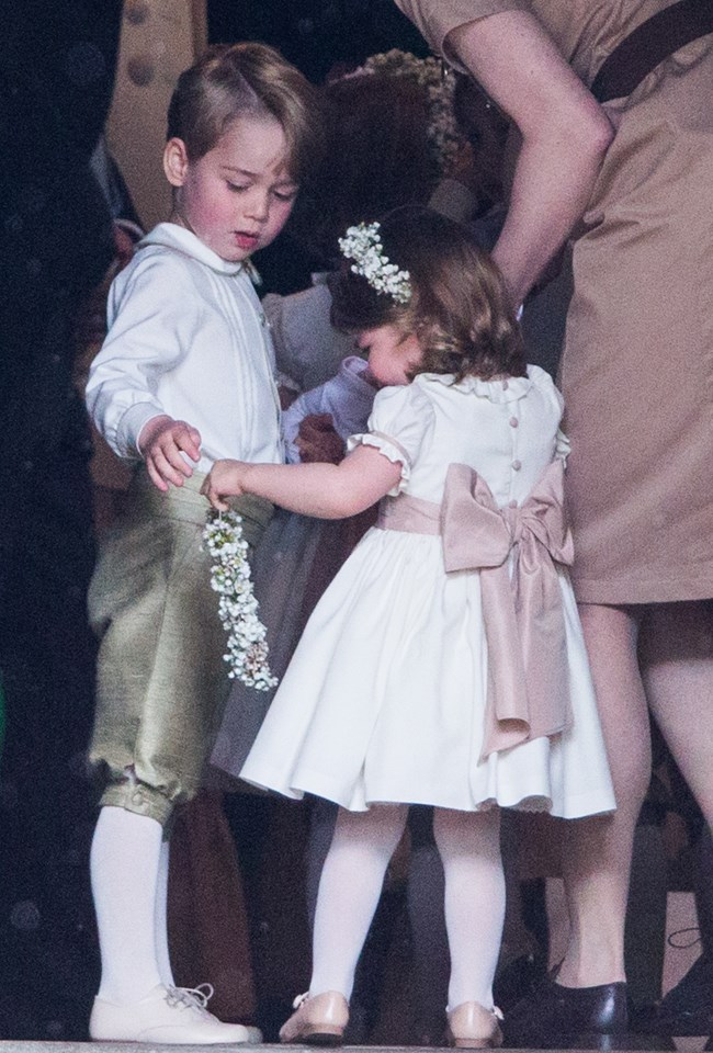 **When George and Charlotte admired another bridesmaid's flower crown**<br> The siblings admired the lily of the valley accessories the bridesmaids wore atop their heads down the aisle.