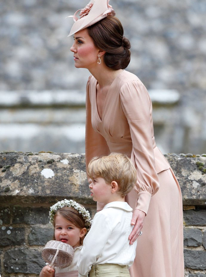 **Charlotte sticking out her tongue in the procession line**<br> The Duchess of Cambridge organised the procession of page boys and bridesmaids that would escort the bride down the aisle. While in line, Charlotte gave the photographers on standby a cheeky smirk–and stuck out her tongue.