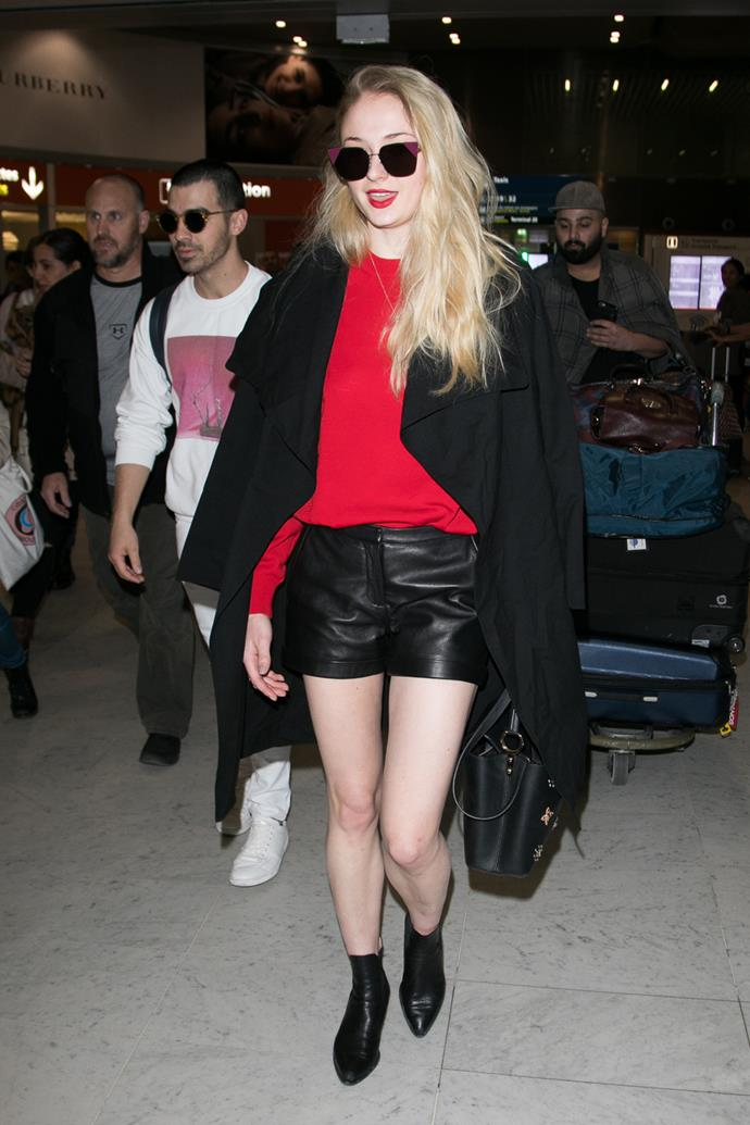 In leather shorts and a chic cape at the airport.