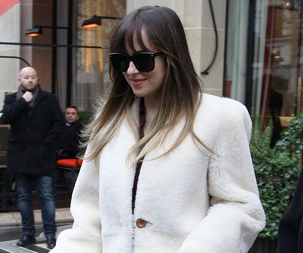 Dakota Johnson walks through the airport with sunglasses on