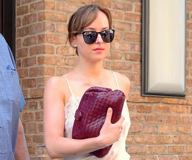 Dakota Johnson walks through the airport with sunglasses on