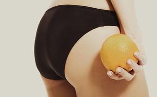 Woman in her underwear holding an orange.