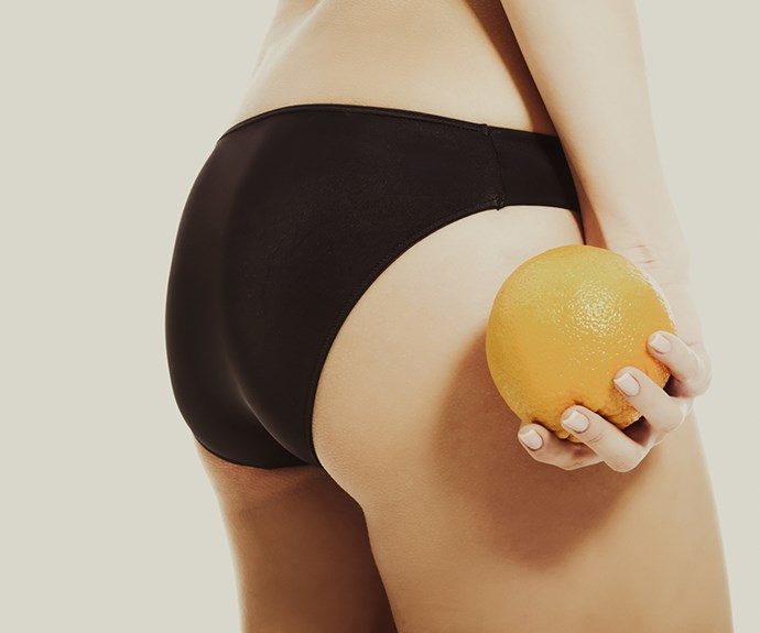 Woman in her underwear holding an orange.