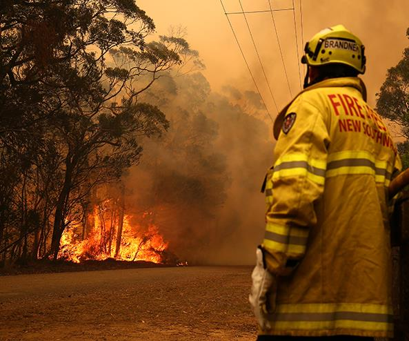 Fire and Rescue personal watch a bushfire as it burns near homes on December 19, 2019 in Sydney, Australia.