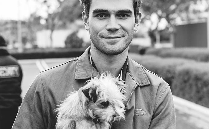 Black and white photo of KJ Apa holding a small dog