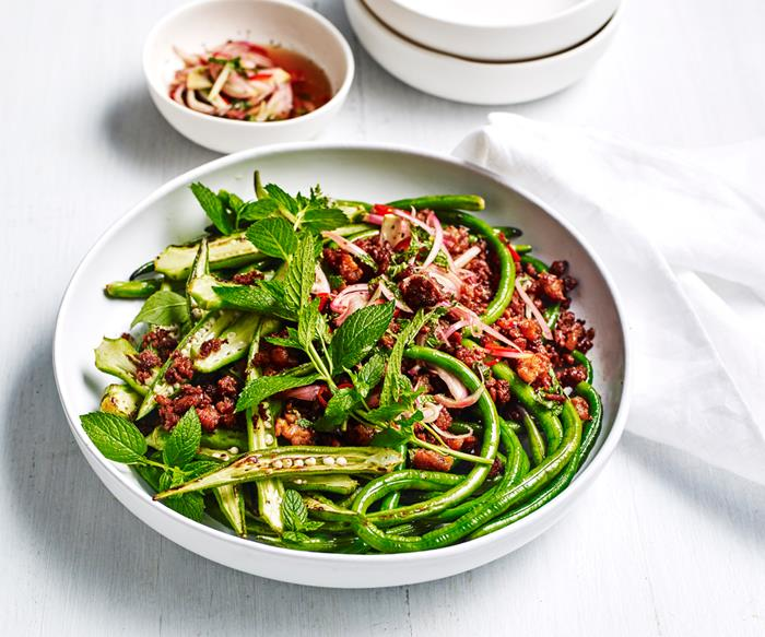 A round white dish with a stir-fry of pork mince, snake beans and sliced okra, topped with mint sprigs.
