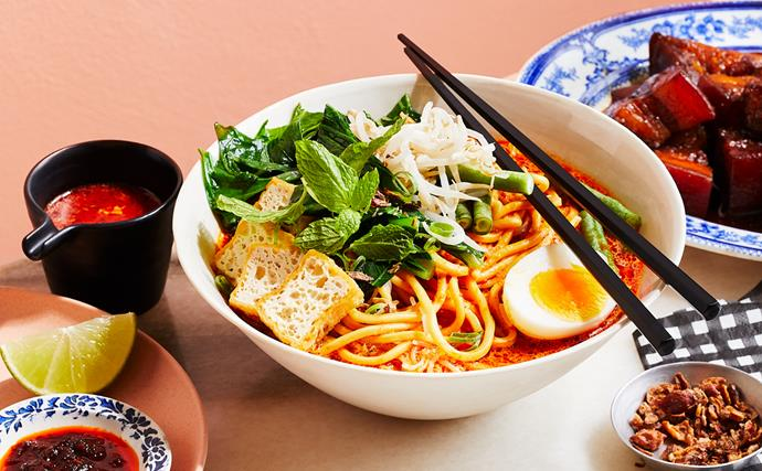 A bowl of curry laksa, with noodles, sliced fried tofu, a halved hard-boiled egg and a sprig of mint, with a pair of black chopsticks laid on top of the bowl.