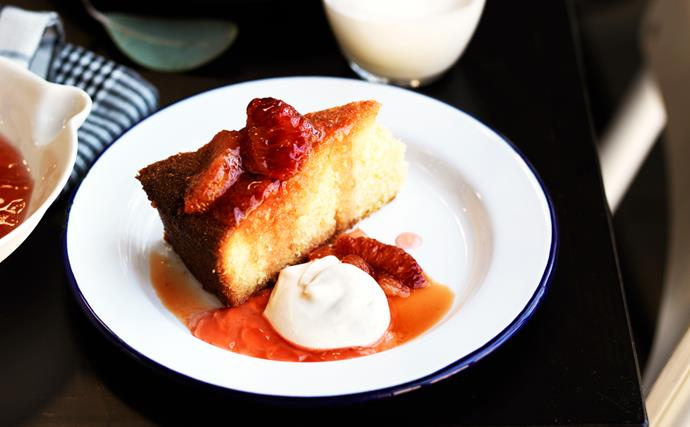 A round cake with a slice cut out of it, topped with segments of blood orange on a white round plate