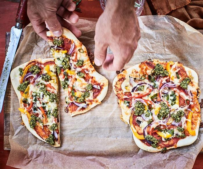person grabbing a piece of vegetarian pizza from chopping board