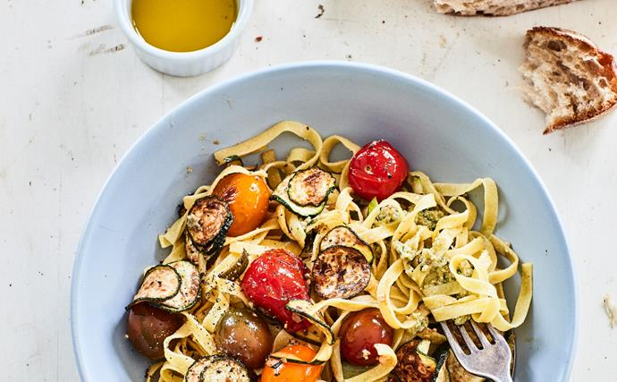 pasta in bowl with courgette tomatoes and pesto