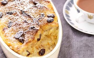 A white oval dish of bread and butter pudding on a grey linen tablecloth.