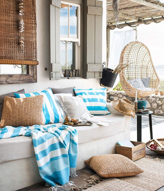**Down by the sea** Sky blue and white nautical-inspired cushions and throws, alongside neutral and wooden accessories.