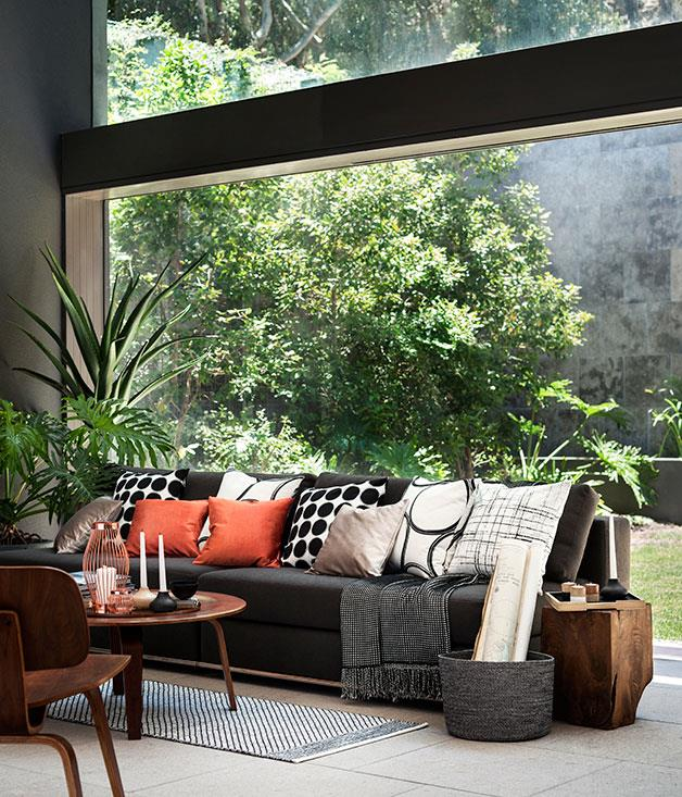 **Colour blocking** Popping orange and boldly printed black and white cushions add drama to the living room.