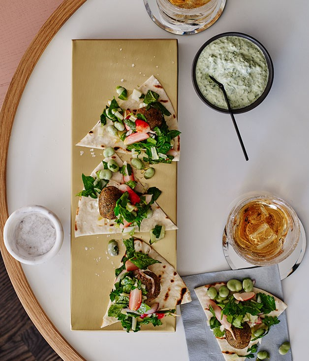Pitas with broad bean felafels, green tahini sauce, pickled radish and herb salad