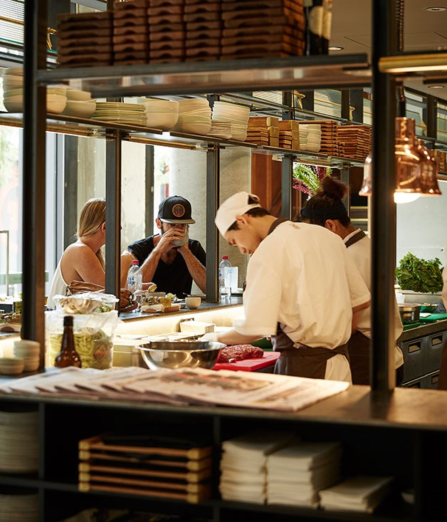 **** Diners look on as chefs work from the open kitchen.