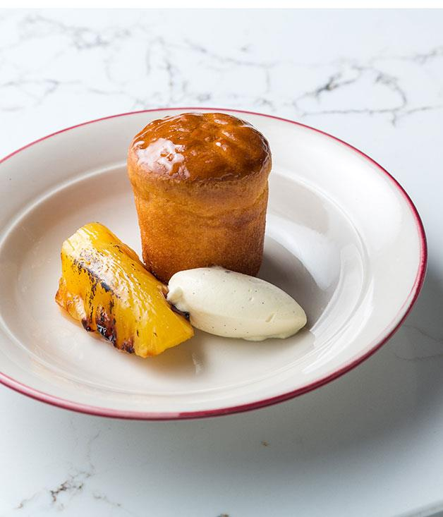 """**Rum baba with rôtisserie pineapple** """"We wanted to use the rôtisserie for not just savoury, but also for something sweet. Roasted pineapple is such a classic. We cook it in a spiced-sugar syrup, slowly first, and then take it out and sit it on a vertical spit that's been custom-designed just for the pineapple. (Yes, really! We had a special bracket made.) The rôtisserie gives the fruit a gorgeous char and smoke, and we baste it with the syrup as it turns.  """"I worked for Philippe Mouchel for many years, first at Restaurant Paul Bocuse in the late '90s. I asked Philippe for Paul Bocuse's rum baba recipe and now it's on the menu at the deli as Philippe's rum baba. It's a classic from one of the greatest chefs who ever lived. And who doesn't love great French rum?"""""""
