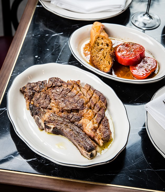 **Chuleta** Porteño's chuleta, a grilled dry-aged rib eye, is served with thick slices of ox-heart tomato and baguette soaked in meat juices and roasted.
