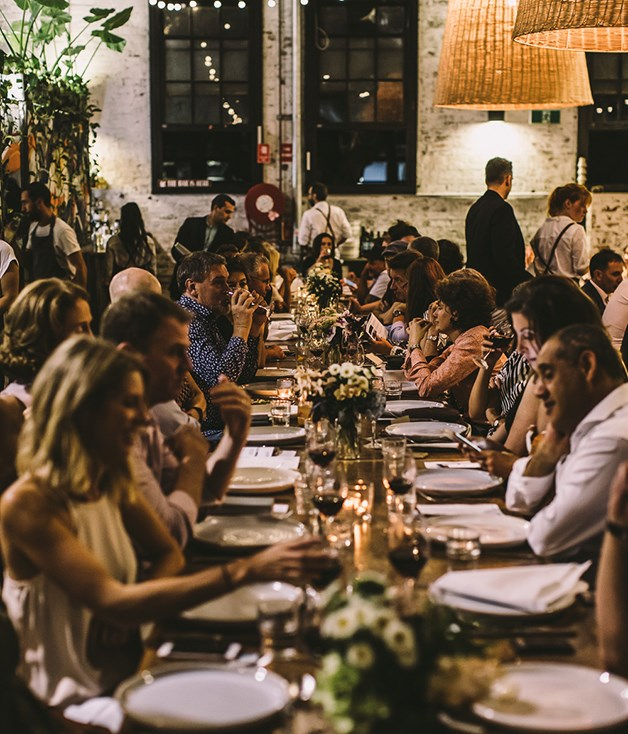 **Guests at #CookForSyria** Long communal tables brought guests together under warm lights.