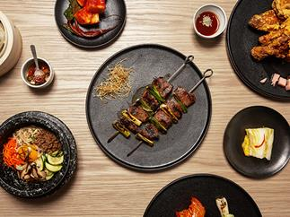An assortment of dishes at Sydney's Sang by Mabasa, including bibimbap, skewers of scotch fillet and spring onion and fried chicken.
