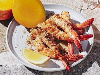 A white pelate with five grilled prawns, with tails attached, spinkled with sesame seeds, and garnished with a lemon wedge and a sliced cheek of mango. The plate is drenched in sunlight.
