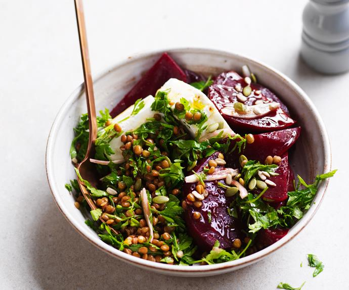 White bowl with salad of chunky chopped beetroot, shredded parsley and brow lentils, with a bronze fork.