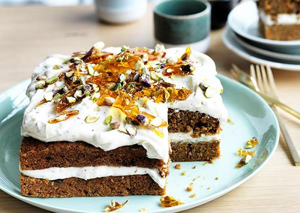 A square carrot cake, topped with cream-cheese icing and pistachios, on a eggshell-blue plate.