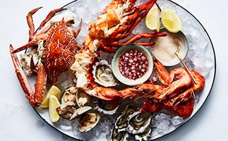 Over the top shot of a large white oval platter laden with seafood: a whole crab, a whole lobster, cooked prawns, clams, and shucked oysters.