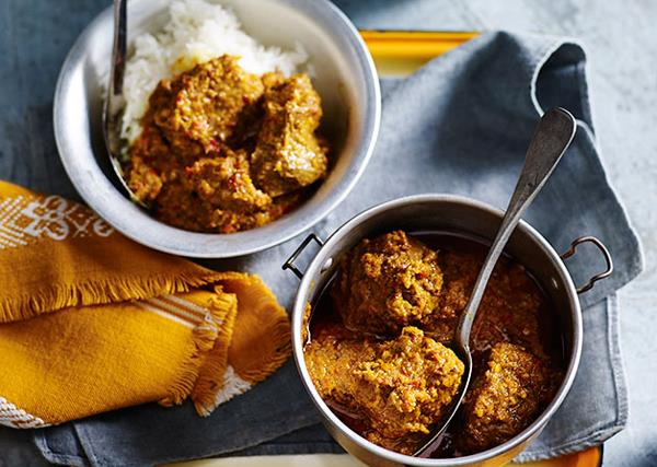 Two bowls with slow-cooked beef rendang curry, on a golden square tray with mustard-yellow and blue napkins.