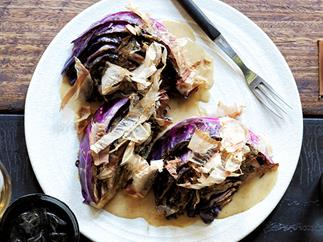 Wedges of purple cabbage, sprinkled with bonito flakes, on a white plate, with a fork