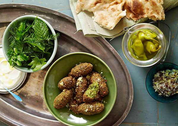 Bird's eye view of a feast, with flatbread in the top-right corner, an open jar of pickled chillies, a green bowl holding fried, oval-shaped falafel, and a white bowl holding a bowl of green herbs.