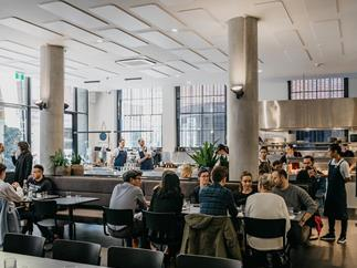 A wide shot of a modern dining room, featuring two grey pillars, and diners.