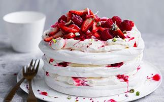 Three-tiered pavlova layered with berry jam, topped with strawberries and raspberries, sitting on a white plate with two brass forks on the side.
