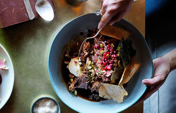 Slow-roasted lamb shoulder with pistachios, pomegranate and vine leaves
