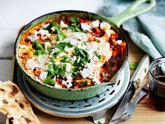 A green frying pan holding a mixture of fried eggs and tomato, topped with crumbled feta and chopped green herbs.