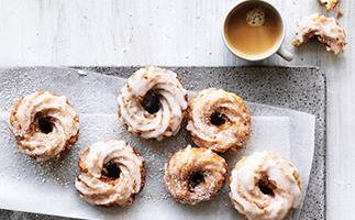 Five round glazed doughnuts with swirled ridges, on a grey rectangular plate, with a cup of tea in the top right corner.
