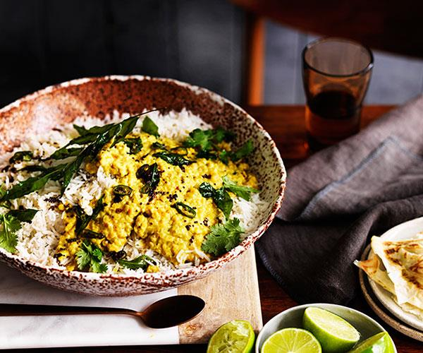 A speckled brown bowl holding white rice, yellow-coloured dhal, and curry leaves.