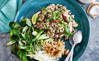 A blue plate with a salad of minced chicken and chillies, a mound of green herbs, shredded white cabbage, and roasted peanuts, with a silver fork and spoon.