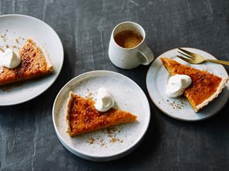 Three white round plates, each holding a triangular slice of golden-baked pumpkin pie, dusted with cinnamon, and served with a dollop of cream.