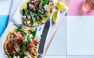 Two round grilled flatbread, topped with asparagus, prosciutto, and ricotta, on a rectangular wooden board wiht a bread knife and lemon segments, sitting on a pink, white and blue tiles.