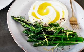 Asparagus spears, sprinkled with lemon zest and dill, with a mound of labne swirled through with olive oil, on an off-white plate with a gold fork.