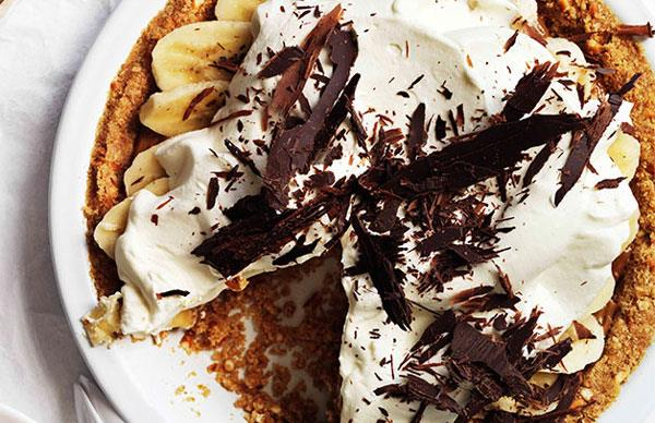 Pie with a golden, crumbly base, topped with sliced bananas, cream and chocolate shavings, with a slice taken out of the pie.