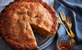 A round, crusty apple pie with a slice taken out of it, sitting on a light-blue linen tablecloth, with golden forks and a tumbler of amber-hued liquid to the side