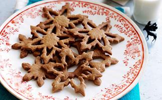 A round white plate, with an ornamental red floral border, holding star-shaped baked cookies.